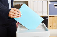 Frau geht wählen mit Stimmzettel