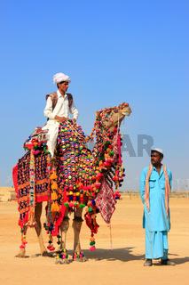 Local man riding a camel at Desert Festival, Jaisalmer, India