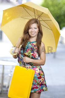 Junge Frau mit Einkaufstasche und Schirm beim shoppen