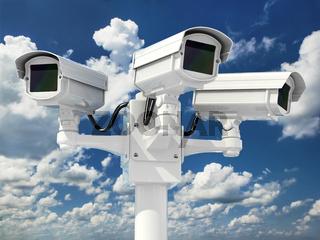 CCTV security camera on cloud sky background.