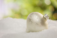 White Christmas Ornament on Snow Over an Abstract Background