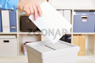 Hand mit Stimmzettel bei Wahl