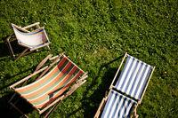Empty deckchairs on a green lawn