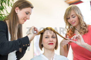 Hairdressers cutting customers hair in salon