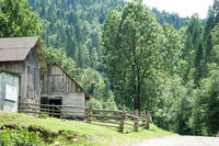 Rural landscape of Carpathian mountains. Small village with traditional wooden houses at sunny day under blue sky