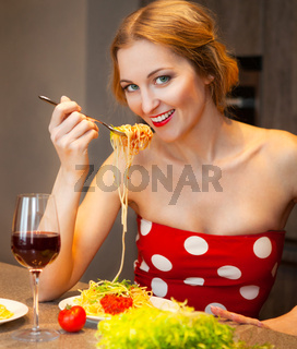 Blond woman eating spaghetti in the kitchen at home