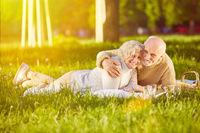 Paar Senioren liegt auf Decke im Park