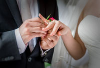 Groom placing a wedding ring on the finger of his bride during a wedding ceremony