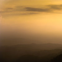 Beautiful sunset sky colors with dramatic clouds and misty mountains silhouette. South India landscape. Munnar, Kerala, India