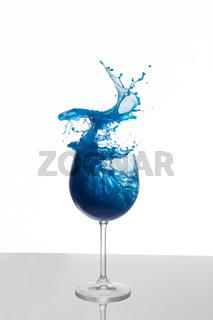 Blaue Flüssigkeit spritzt aus einem Glas