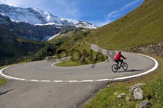 Biker radelt auf einem Mountainbike in einer Haarnadelkurve auf der Bergstrasse zum Klausenpass vor den Glarner Alpen bei Urnerboden