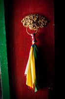 Old door at Buddhist monastery temple decorated with ancient doorknob and tassel. India, Ladakh, Likir Gompa
