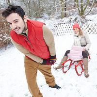 Paar beim Schlittenfahren zu Weihnachten