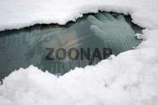 Junge Frau schaut aus einem verschneiten Auto