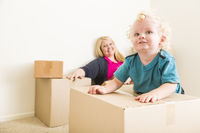 Happy Mother and Son in Empty Room with Moving Boxes
