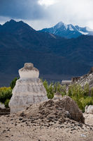 Buddhist stupa ( chorten ) over Himalaya high mountain landscape with cloudy blue sky India, Ladakh, Leh valley