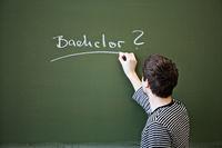 Young man writing Bachelor on a chalkboard