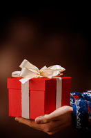 two hands holding a red gift with white ribbon