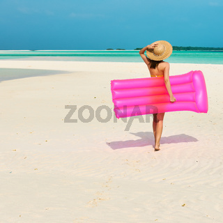 Woman with pink inflatable raft at the beach