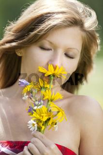 Maedchen riecht an Blumen