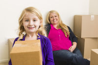 Young Mother and Daughter In Empty Room With Moving Boxes