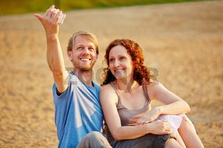 Glückliches Paar macht Selfie am Strand
