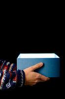 blaue Geschenkbox offen vor schwarzem Hintergrund