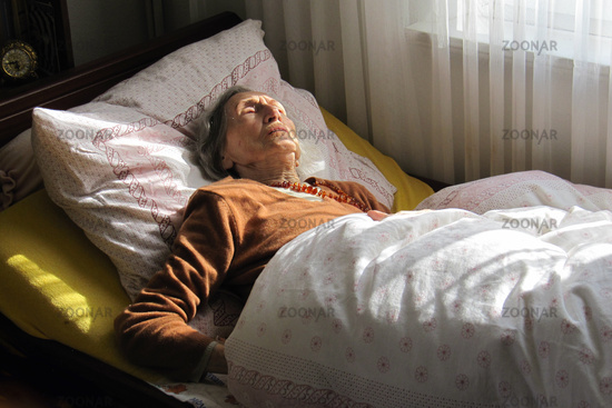 Old woman sleeping in her bed