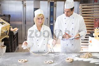 Baker instructs apprentice how to form pretzel