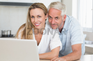 Happy couple using laptop together at the counter