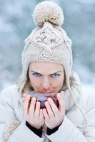 Frau im Winter pustet in Tasse mit Tee