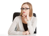 Portrait of beautiful attractive woman in eyeglasses. She's sitting by a desk.