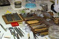 Arbeitsplatz mit Arbeitsuntensilien für die Uhrmacherei / Workplace with tools for assembling watches