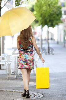 Junge Frau mit Einkaufstasche und Schirm