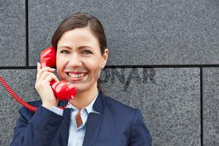 Lächelnde Geschäftsfrau telefoniert mit rotem Telefon