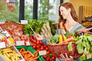 Frau mit Einkaufszettel kauft Gemüse im Bioladen