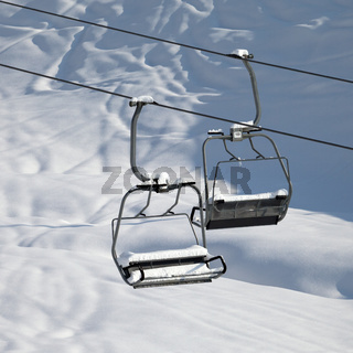 Two chair-lift with snowdrift in sun morning. Close-up view.