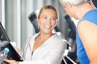 Fitnesstrainer hilft Senior am Laufband