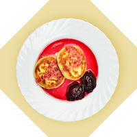 Dish of pancakes with cherry sause on white plate.