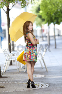 Junge Frau mit Einkaufstuete und Schirm beim shoppen
