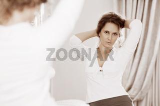 Beautiful woman looking in the bedroom mirror