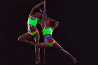 Two slender girls with UV makeup posing near pylon