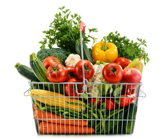 Wire shopping basket with groceries isolated on white background