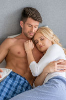 Couple Wearing Pajamas Snuggling in Bed