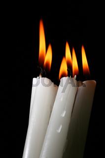 sacred candles in dark on black background