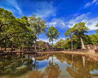 Ancient Khmer architecture. Outdoor park landscape with lake and panorama view of Baphuon temple ruins at Angkor Wat complex, Siem Reap, Cambodia