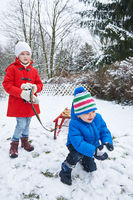 Kinder spielen mit Schlitten im Winter im Schnee