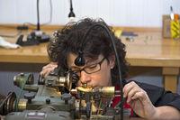 Frau mit einer Augenlupe produziert Präzisionsteile für Uhren an einer Drehmaschine