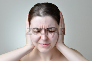 Young woman covering her ears