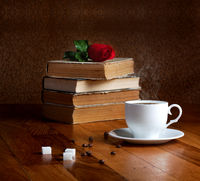Hot cup of fresh coffee on the wooden table and stack of books to read with red rose